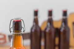 Close up of an unopened beer bottle. Close up of an unopened brown glass beer bottle with a wire stopper lid with three further blurred unlabeled bottles in the Stock Image