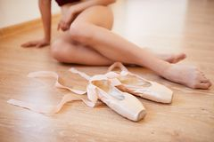 Ballerinas feet and pointe shoes. Close-up of unrecognizable ballerina with beautiful legs sitting on floor with pointe shoes in ballet studio royalty free stock image