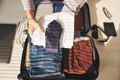 Preparing for journey. Close up of unrecognizable businessman packing suitcase for business trip Stock Image