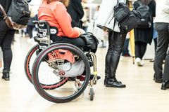 Close up of unrecognizable hanicapped woman on a wheelchair queuing in line to perform everyday tasks. royalty free stock photo