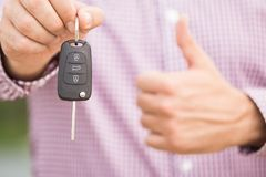 Man holding car key with thumbs up. Car dealership and rental concepts. stock image