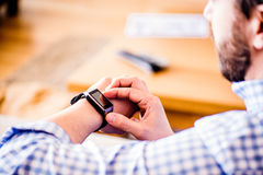 Close up of unrecognizable man using smart watch. Close up of unrecognizable man in blue checked shirt using smart watch Stock Photography