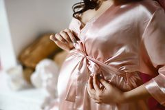 Close-up of unrecognizable pregnant happy woman with hands over tummy in a pink satin robe with a bow stock photos