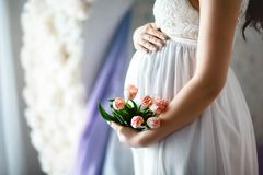Close-up of unrecognizable pregnant woman with hands over tummy in white lace dresses with pink spring tulips.  Royalty Free Stock Photography