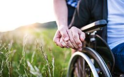 A close-up of unrecognizable son holding his father`s hand on a wheelchair. Copy space stock photo