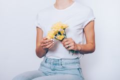 Close-up unrecognizable woman wearing white t-shirt. And blue jeans sitting over white background holding small bouquet of yellow daisies royalty free stock image