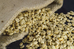 Close-up of unroasted coffee beans in hemp bag on black background. Royalty Free Stock Photos
