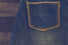 Close up up of fancy washed blue jeans pocket. On oak wood texture background, Ripped jeans of a stack Hipster fashion copy space. For text. Perfect for your stock images