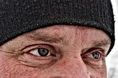 Eyes tired, with wrinkles around, Mature men, tired and sad looking forward and up. Close-up upper part of the face of an adult man in a black winter hat with a Royalty Free Stock Photos