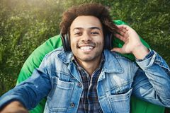 Close-up upper view shot of handsome african man with afro hairstyle extending hand towards camera while listening music stock images