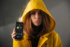 Close up of an upset girl dressed in raincoat. With a hood on her head standing behind a wet with rain window and showing mobile phone with a weather app on a Royalty Free Stock Image