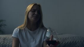 Close up of upset girl with a glass of wine. Feeling miserable. Close up of young girl sitting at her bed while drinking wine and having sad emotions stock video