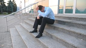 Close up of upset sad manager sitting on stairs near office building and crying. Desperate young businessman got a very. Bad news on phone and feeling despair stock video