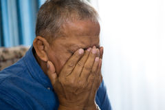 Close up of upset senior man covering eyes with hands Royalty Free Stock Photos