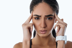 Close up of upset woman looking frustrated. Have a headache. Sad female touching her temple with fingers looking straight at camera wearing smart watches Royalty Free Stock Image
