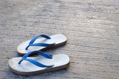Close up used white and blue rubber slippers on an old concert. stock photos