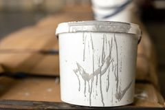 Close-up used white dirty plastic paint bucket in room. Renovation and repair process concept. Copyspace, product. Placement. Place fot rext royalty free stock image