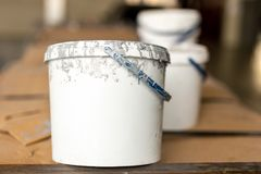 Close-up used white dirty plastic paint bucket in room. Renovation and repair process concept. Copyspace, product placement. Place. Fot rext stock photos