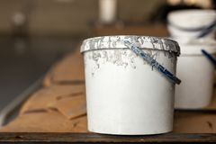 Close-up used white dirty plastic paint bucket in room. Renovation and repair process concept. Copyspace, product placement. Place stock photo