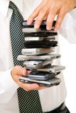 Close-up of usinessman holding stack of phones Stock Photos