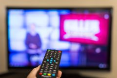Close up Using Remote Control and Watching Television. Hand holding TV remote control Royalty Free Stock Photography