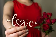 Valentines day love sign and red roses, beautiful woman in red dress holding love cupid arrow in hand,close up stock photo