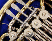 Close up of the valves and keys of a french horn. Close up of the valves and keys of a concert french horn on a dark blue background Stock Photography