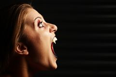 Close up of a vampire woman's mouth. Over dark background Royalty Free Stock Photos