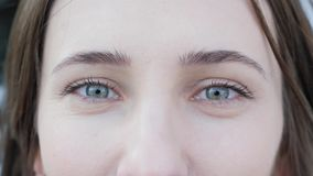 Close-up van aantrekkelijke mooie vrouwen blauwe ogen wordt geschoten met die het lichte dag samenstelling en concentreren het be stock video