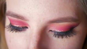 Close-up van aantrekkelijke vrouwelijke blauwe ogenmake-up met roze schaduwen en gouden eyeline die camera bekijken stock video