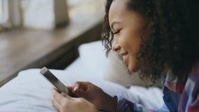 Close-up van Afrikaanse meisje het letten op foto's online op smartphone terwijl thuis het liggen op bed Stock Foto's