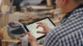 Close-up van arbeider wat betreft het tabletscherm met ontwerp van met de hand gemaakt meubilair stock footage