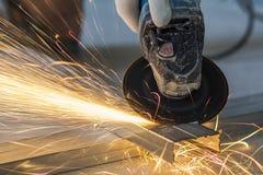Close-up van arbeiders scherp metaal met molen Vonkt terwijl grijns Royalty-vrije Stock Foto