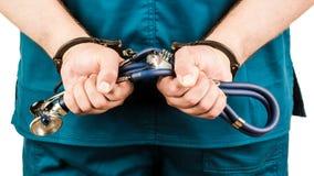 Close-up van Arts Hands With Stethoscope in Handcuffs Conc stock afbeeldingen