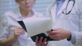 Close-up van artsen die op de anamnese letten stock video