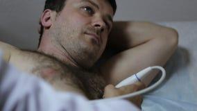 Close-up van artsenhand die medische ultrasone klank mannelijke patiënt doen stock videobeelden