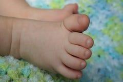 Close-up van Baby` s Voeten op een Blauwe en Groene Deken stock afbeeldingen