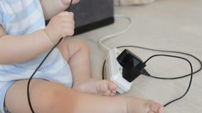 Close-up van babyjongen het spelen met kabels en elektrische uitbreidingskabels Concept kind in gevaar stock video