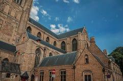 Close-up van bakstenen muren en daken van een kerk, tegen blauwe zonnige hemel in Brugge Stock Afbeeldingen