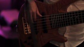 Close-up van Bass Player Hands Playing Rock-Muziek met Bass Guitar bij het Overleg in de Nachtclub stock video