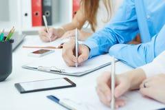 Close-up van bedrijfsmensenhanden die nota's over commerciële vergadering maken op kantoor Stock Afbeeldingen