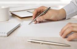Close-up van bedrijfsvrouwenhand die op papier bij bureau schrijven Royalty-vrije Stock Afbeeldingen