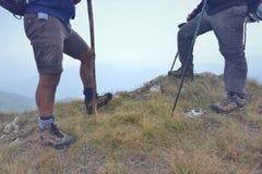 Close-up van benen van jonge wandelaars die op de weg van het land lopen Het jonge paarsleep wekken Nadruk op wandelingsschoenen Stock Afbeelding
