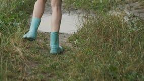 Close-up van benen in laarzen die van meisje in de vulklei van de de zomerregen bij de landweg lopen stock videobeelden