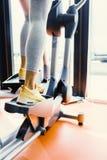Close-up van benen van een wijfje wordt geschoten die elliptische trainer gebruiken die Royalty-vrije Stock Foto