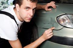 Close-up van beschadigde auto die door werktuigkundige wordt geïnspecteerdÀ Stock Afbeelding