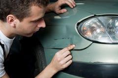 Close-up van beschadigde auto die door werktuigkundige wordt geïnspecteerd Stock Foto's