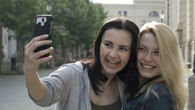 Close-up van beste meisjesvrienden die samen een selfie met een smartphone op een stedelijk gebied betekenen stock video