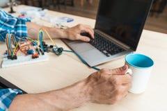 Close-up van bezige programmeurshand met koffiekop Stock Foto's