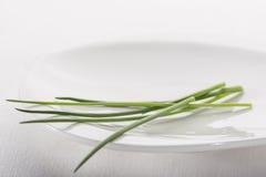 Close-up van bieslook op witte plaat Stock Foto